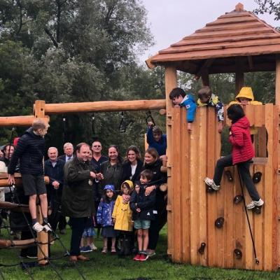 a photograph of adults and children beside wooden play equipment. Click, tap or press enter to open a full article