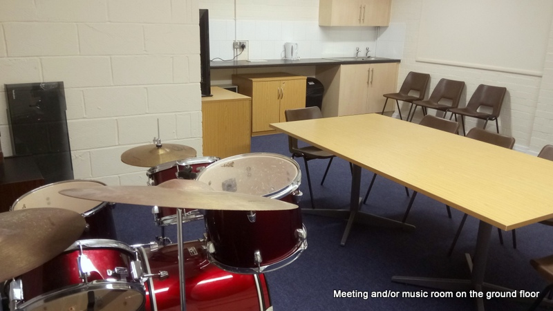 a room with musical instruments and a small kitchen facility