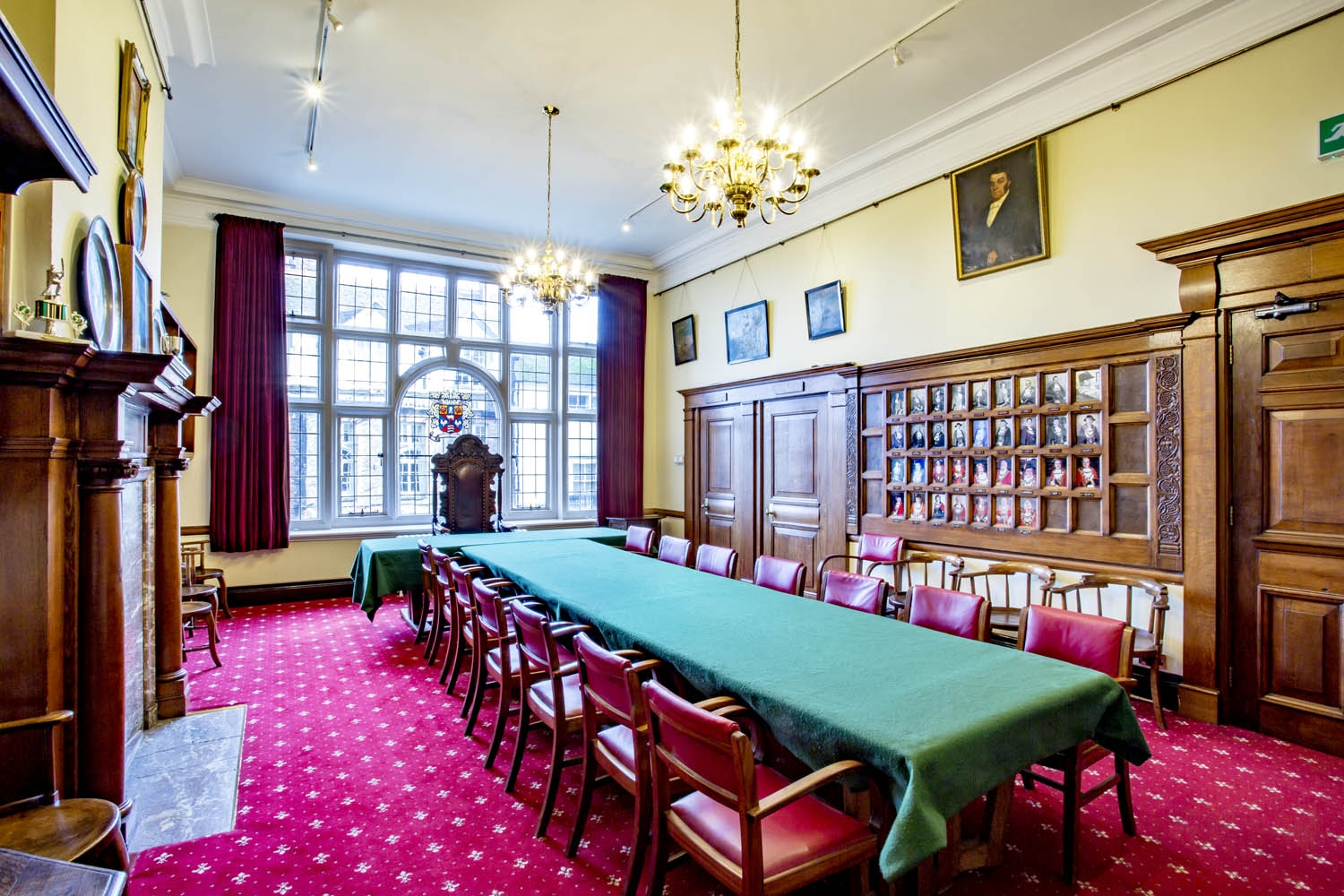 A grand, panelled room lined with portraits.  A very large window takes up one wall with a stained glass crest. A long table is lined by wooden and leather chairs