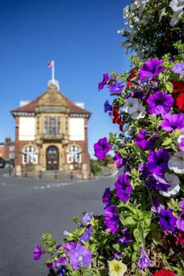 An imposing building - Marlborough Town Hall - stands at the centre of a road. There is a display of flowers in the foreground