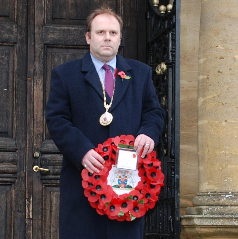 A smartly dressed man stands in front of a building.  He holds a wreath of poppies