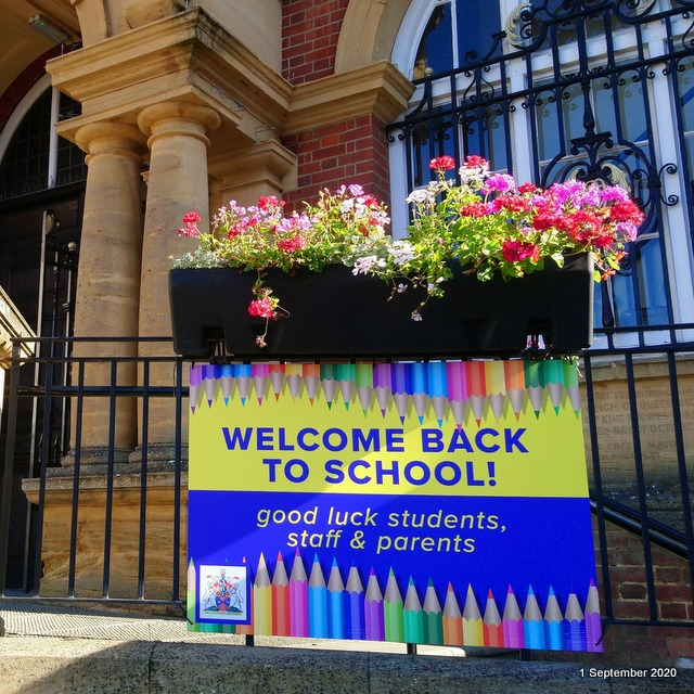 a bright and colourful sign wishing staff, students and parents good luck returning to school is attached to metal railings. There is a trough of flowers above and a brick and stone building behind