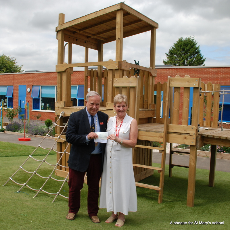 a man and woman are holding a small piece of paper.  Behind them is a play structure, with a school building in the background