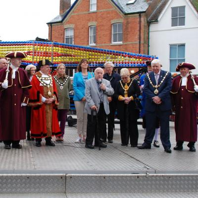 An elderly gentleman wearing a grey suit is standing and speaking into a microphone.  He is surrounded by people in formal dress, gowns and chains standing on a fairground ride