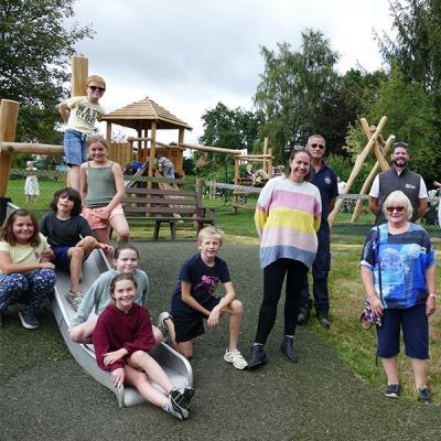 children are sitting on a slide, smiling to the camera.  Adults stand to the right. Behind them are wooden play structures