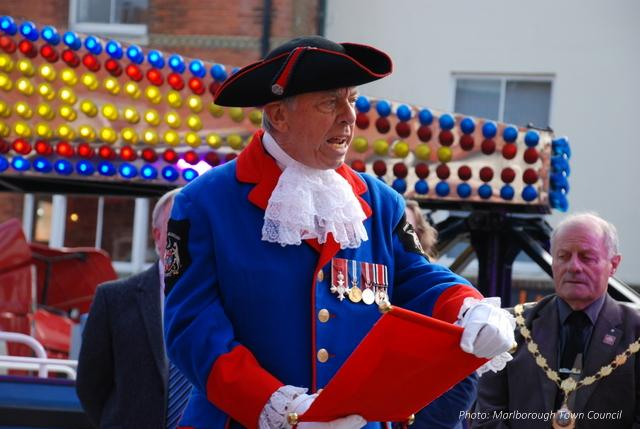 A man in a ceremonial blue coat and tricorn hat reads aloud from a scroll