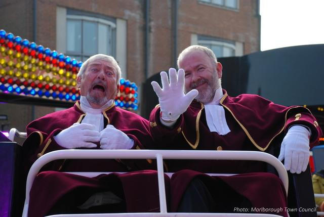 Two men in ceremonial robes pull faces as a fairground ride begins