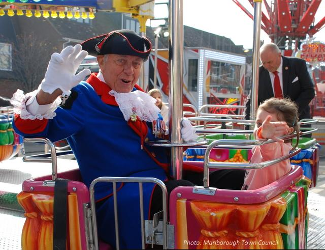 A man in ceremonial dress and a small girl enjoy a fairground ride