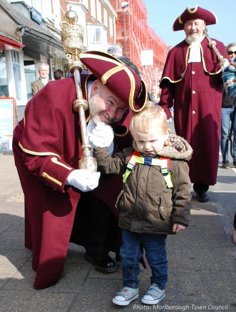 A small child is accompanied by two men in ceremonial dress