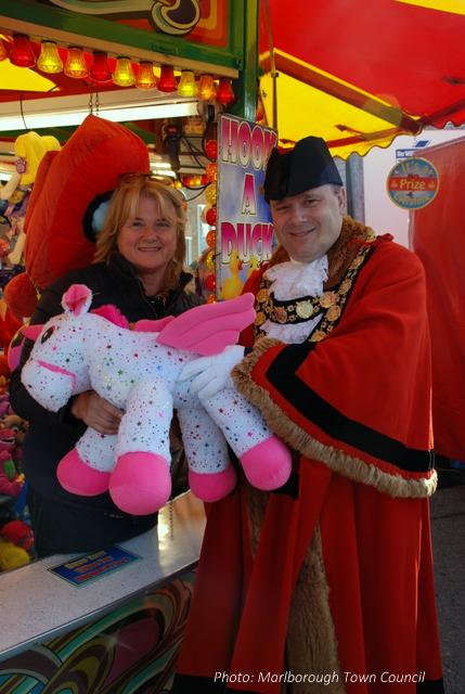 A man and woman smile at the camera.  They hold a large soft toy unicorn