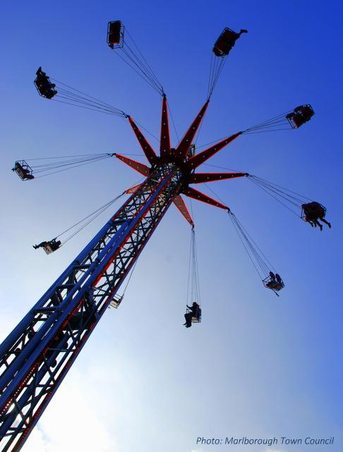 A fairground ride swings people around a pole at a great height